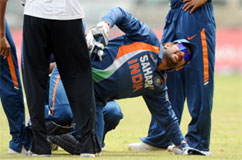 Indian cricket team captain and wicketkeeper Mahendra Singh Dhoni (C) reacts after get hurt. AFP