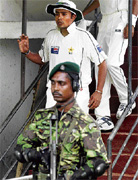 A Sri Lankan security personnel takes guard as Pakistani bowler Danish Kaneria steps out of the dressing room. AP