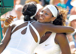 All in the family: Serena Williams is congratulated by sister Venus Williams after their singles finals at the Wimbledon in  London on Saturday. Reuters