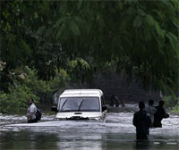 A disaster management vehicle is seen submerged in water after it came to inspect the water levels at the neighboring Indian Airlines colony next to Mithi River in Mumbai, India, Tuesday, July 14, 2009. Heavy showers delayed commuter trains Tuesday, causing massive traffic snarls in Mumbai. AP Photo