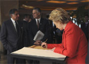 US Secretary of State Hillary Rodham Clinton signs a memorial guest book at the Taj Mahal hotel in Mumbai, Saturday. USIS photo