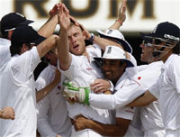 England's Andrew Flintoff, centre, is congratulated by his team mates after bowling the wicket of Australia's Nathan Hauritz for 1 run. AP