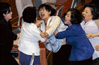 An opposition legislator screams after being dragged away by ruling party lawmakers during a scuffle in South Korean parliament in Seoul on Wednesday. AFP