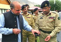 In this picture taken on September 8, 1999, then Pakistani Prime Minister Nawaz Sharif (L) looks at the pistol of Army Chief General Pervez Musharraf (R) during a visit in Skardhu to the bereaved families of soldiers killed in Kargil Conflict between Pakistan and India. AFP