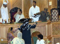 Opposition leader Mehbooba Mufti tries to throw a mike to the Speaker inside J&K Legislative Assembly demanding probe on Shopian rape and murder case in Srinagar on Monday. PTI