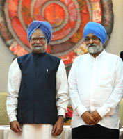 Prime Minister Manmohan Singh (L) and Deputy Chairman of the Planning Commission Montek Singh Ahluwalia pose for the media on Monday. AFP