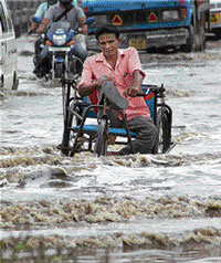 A handicapped person wades through a waterlogged road after heavy rains in Gurgaon on Tuesday. PTI