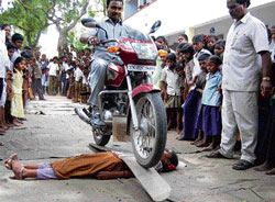 A motorcyclist riding on a plank placed over a schoolgirl during a bravery show organised by a government elementary school in Villupuram in Tamil Nadu. AFP