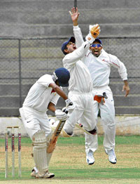 President XI's wicket-keeper Vinay Uthappa  (centre) celebrates with skipper Robin Uthappa (right) after taking a sharp catch to dismiss Combined XI's Abrar Khazi in Bangalore on Tuesday. DH Photo