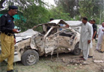 Pakistani police officials examine a badly damaged vehicle after a bomb exploded in the parking lot of a northwestern Pakistani town. AFP