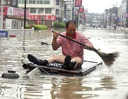 A man wades through the flooded street in a home-made raft in Cangnan, east China's Zhejiang province, on Monday. Xinhua