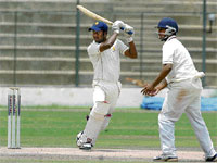 Classy Shot: KSCA XI's CM Gautam cuts en route to his hundred against President's XI on Wednesday. DH photo