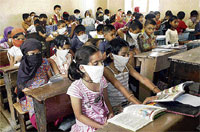 Scare In School: Students wear masks as a precaution against the H1N1 virus inside a classroom in Sangli, Maharashtra, on Wednesday. PTI