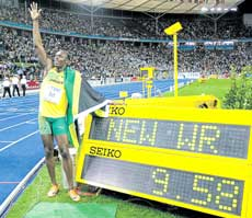 Jamaican Usain Bolt proudly poses next to the screen announcing a new world record in the men's 100 metres. AP