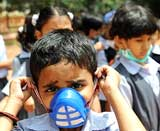 Schoolchildren wearing protective masks in a school in Bangalore . File Photo AFP