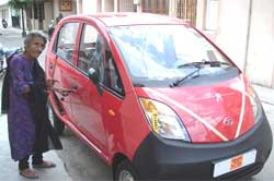 96 years old Homai Vyarawalla, India's first woman photojournalist, stands next to a Nano car at her residence in Vadodara on Tuesday. Tata motors delivered this car to her from its priority quota. PTI