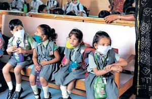 Schoolchildren wear masks at a school where doctors perform examinations in Ahmedabad on Tuesday as the death toll due to swine flu in Gujarat rose to three. AFP