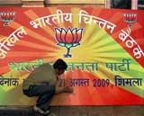 A worker cleaning a board of BJP's