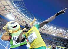 Jamaican Usain Bolt celebrates with mascot Berlino after winning the 200M gold at the World Athletics Championships on Thursday. Reuters