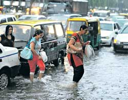 Pedestrians cross a flooded road during a sudden downpour in New Delhi on Friday. AFP