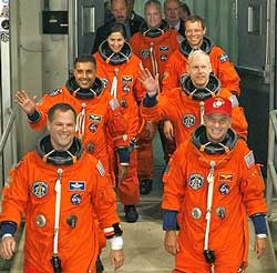 Crew members of space shuttle Discovery leave the Operations and Checkout Building on Monday night. AP