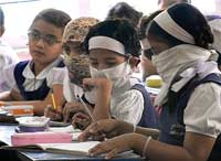 Students wearing respiratory masks attend class in Pune on Monday. PTI