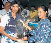 FINE MOMENT: Prakash Jolly (left) receives the under-19 State badminton titles from former sprinter Ashwini Nachappa in Davanagere on Friday. DH photo