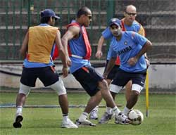Coach Gary Kirsten, background right, and cricketers, from left, Abhishek Nayar, Yousuf Pathan and Dinesh Karthik play a game of soccer