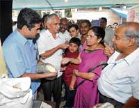 Did You Like It?: Food and Civil Supplies Minister H Halappa interacting with buyers during his visit to Janata Bazaar in Bangalore on Sunday. MLA Vijaya Kumar is also seen. DH photo