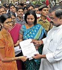 Higher Education Minister Arvind Limbavali handing over the placement order to a candidate selected as lecturer in a Government Degree College. Collegiate Education Commissioner Nagambika Devi is also seen. DH PHOTO