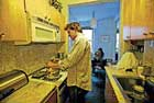 Colin Beavan prepares breakfast on the gas range in their New York apartment. In the background is wife Michelle Conlin and their two-year-old daughter. NYT