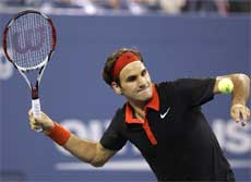 Roger Federer hits a tennis ball into the stands after defeating Simon Greul in the second round of the US Open tennis tournament in New York on Wednesday. AP