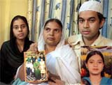 Shamima Kausar, mother of Ishrat Jahan (inset), holds a group photo of the family while standing with her daughter and son in Thane, Mumbai on Monday. PTI