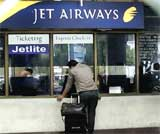 A passenger makes an inquiry at a deserted Jet Airways counter at the airport in Calcutta on Tuesday. AP