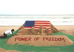 Sand artist Sudarsan Pattnaik creates a sand sculpture to commemorate the 8th anniversary of 9/11 terrorist attack on World Trade Centre, at Puri in Orissa on Thursday. PTI