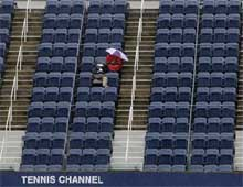 Spectators sit in Arthur Ashe Stadium waiting for play to commence despite the heavy rain at the U.S. Open tennis tournament in New York. AP