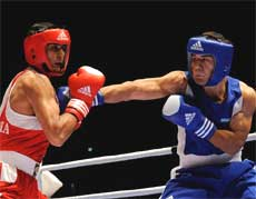 India's Vijender Kumar (L), fights against Abbos Atoev, of Uzbekistan, during a men's middleweight 75 kg semifinal boxing match at the World Boxing Championships, in Milan Friday.