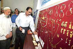 Police Commissioner Shankar Bidari looks at the gold and money that was stolen from Akhtar Nagaria's house. Akhtar Nagaria (left) is also seen. DH Photo