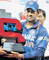 PROUD POSSESSION: Mahendra Singh Dhoni holds the Compaq Cup on Tuesday. AP