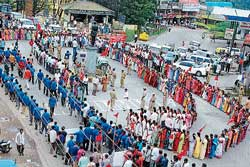 Hundreds of labourers staging a protest urging fulfilment of various demands by forming a human chain at General Thimmaiah Circle in Madikeri on Tuesday. DH Photo