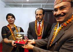 A temple official, right, presents a replica of the Pashupatinath temple to Indian Foreign secretary Nirupama Rao, left as Indian ambassador to Nepal Rakesh Sood, center looks on during a visit by the former in Katmandu, Nepal on Tuesday. AP