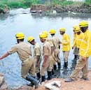 Emergency services personnel conducting search operations at Madiwala lake in Bangalore on Thursday.  DH Photo