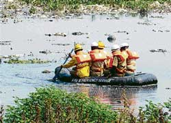 Fire personnel searching for the missing boy at Madivala lake for the third day. DH PHOTO