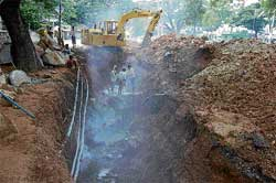 Repair: Workers engaged in repairing drainage near the police station circle in Kolar. DH photo