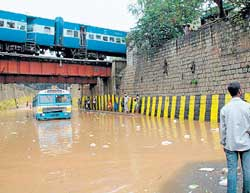 Messy situation: A BMTC bus stuck in rain water under the bridge near Kino Theatre in  Bangalore on Friday. DH photo