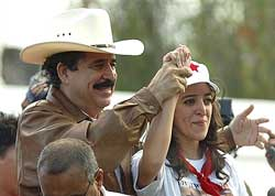 Honduras' ousted President Manuel Zelaya and his daughter gesture to supporters from Brazil's embassy in Tegucigalpa on Monday. AP
