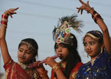 Indian artists dressed in traditional attire dance during Dussehra procession