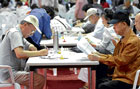 yet to give up: People complete an application form at a job fair for people 60 and older in Seoul on June , 2009.  NYT