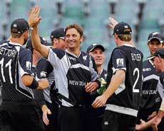 New Zealand's pace bowler Shane Bond (centre) celebrates with his team-mates  the dismissal of England's Joe Denly at Johannesburg on Tuesday. AFP
