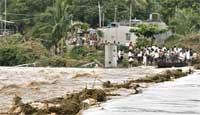 Stranded villagers wait for water levels to recede to cross over to the other side as floodwaters overflow in Kudadarahal village on Saturday. AP